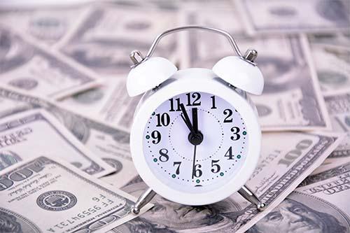 Reloj depertador sobre dinero