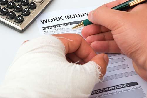 Mano dañada firmando un formulario de Compensación Laboral form
