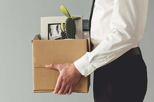 Hombre con caja de papelería de oficina